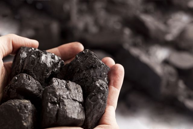 A hand holding a piece of coal